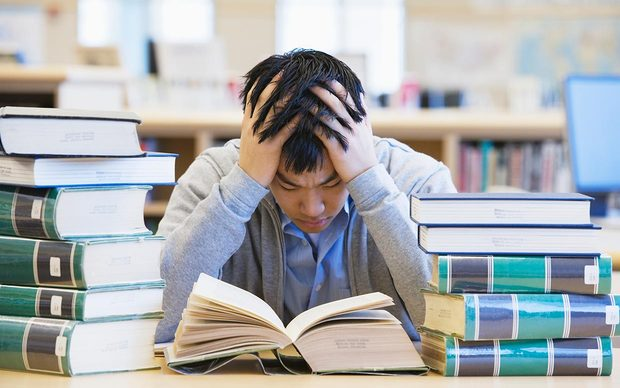 Photo of someone studying behind piles of books