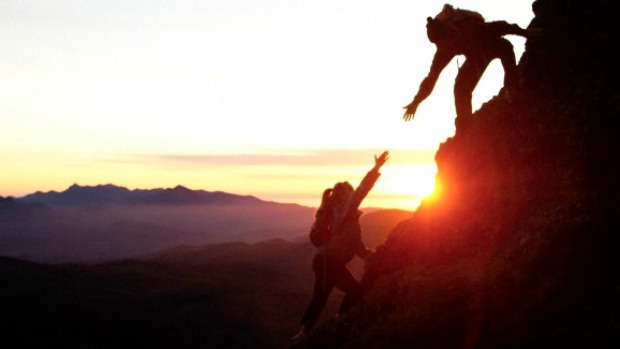 People helping each other to climb a mountain