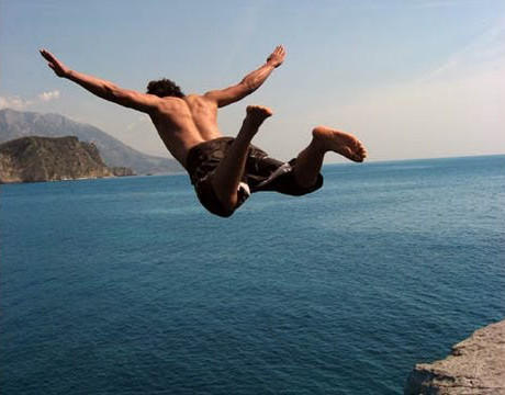 A guy jumping from a cliff into the sea