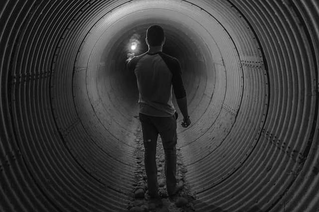 Picture of someone holding a light, alone in a tunnel. Incremental Software Development helps to avoid the tunnel effect when performing a large scale refactoring