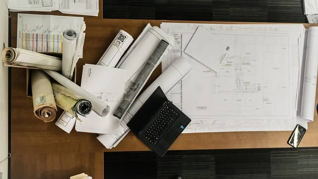 Photos of a desk littered with detailed architecture plans. Big Design Up Front is a lot of speculative work