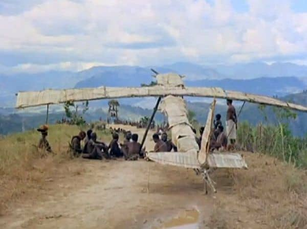 A photo of people sitting in front of a 'Cargo Cult' wooden plane