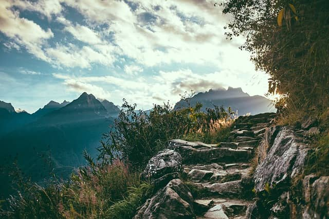 Photo of a mountain path where we can guess the sun will appear at the next turn. Design-Level Event Storming is a step by step workshop that leads to great outcome.