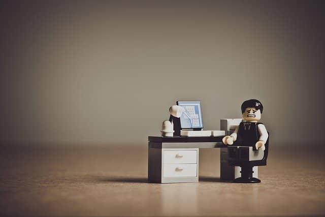 A lego character at his desk looking stressed out by too much work. Spending many weeks to test a legacy code bug is not justifiable.