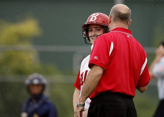 A photo of a softball coach giving advice to a player. Technical Agile Coach is a lot like sports coaching.