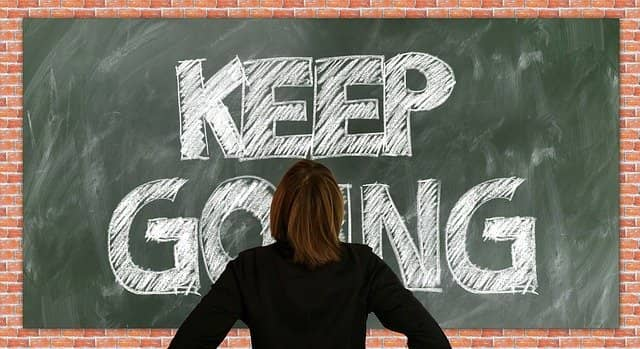 """A photo of someone standing in front of a black board with """"Keep Going"""" written on it. Succeeding to sell your technical coaching services internally is mostly of matter the finding the way to do so, keep going until you find how!"""