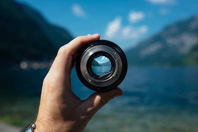 Photo of a lens in front of a landscape. Being able to focus, even in remote work, is key to energized and sustainable work. When coaching a remote team with pair programming, we must show the example and make sure to stay super-focused.