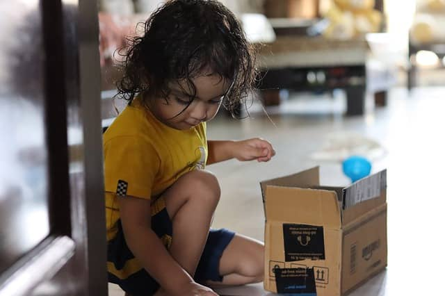 Photo of a young child who just opened a delivery box. Deliveries are like presents. We can share the joy of discovering what's in it for us with our remote pair programming buddy.