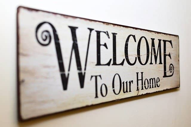 Photo of a sign written 'Welcome to our home'. Running a 'home tour' with your pair programming buddy is a fun remote collaboration tip that will kick off constructive work.
