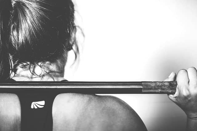 Black and White photo from behind of someone who's holding a weight bar on his shoulders. Instead of wondering 'How to coach a team to TDD, simply using TDD as a workout exercise helps everyone to get over any prior misunderstanding about TDD.