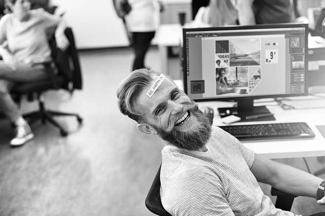 Photo of a man smiling and sitting at his desk in an open space. Spend the minimum time with the laggards and focus on enthusiastic people instead.