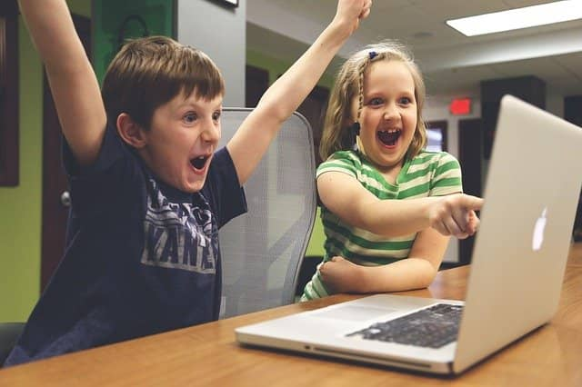 Photo of 2 kids pairing at a computer, and raising arms in the air in a sign of victory. Playing with TCR and git handover script made us discover the power of gamification when doing technical agile coaching. Yet one more aspect where the pandemic lead us to better ways of working
