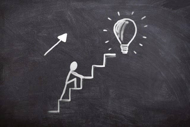 Chalk drawing of a stick person climbing steps until he reaches a bulb symbolizing an idea. Innovation often comes from difficulties and constraints. In our case, the pandemic was a key factor that forced us into finding better ways of doing technical agile coaching